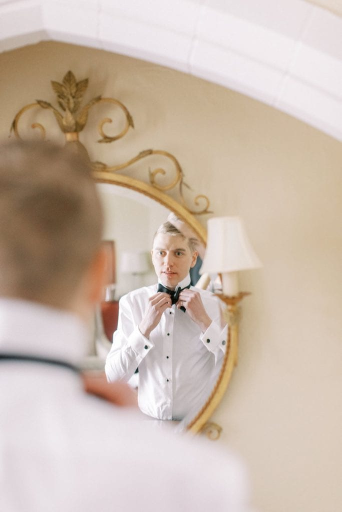 Banff wedding photography groom  getting dressed mirror